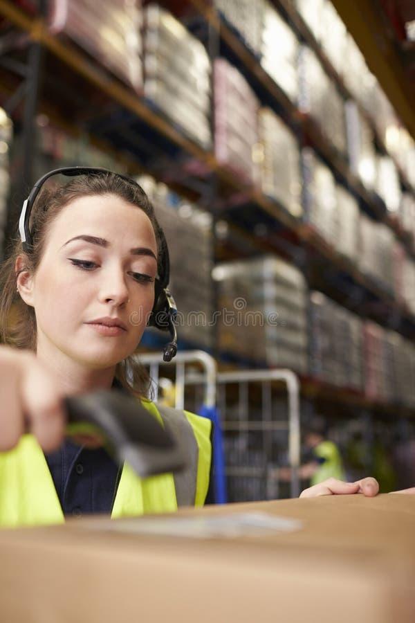 De vrouw gebruikt streepjescodelezer in een pakhuis, verticaal close-up stock fotografie