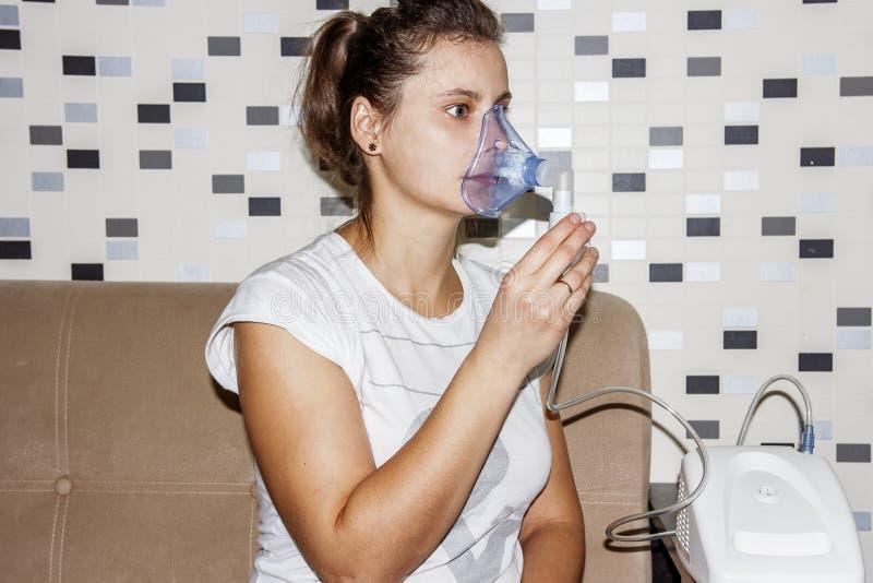 De vrouw gebruikt thuis een inhaleertoestel wanneer zij hoest Behandeling van ademhalingsziekten Inhalatie met bronchitis stock afbeelding