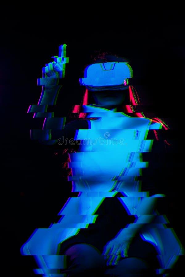 De vrouw gebruikt virtuele werkelijkheidshoofdtelefoon Beeld met glitch effect stock foto