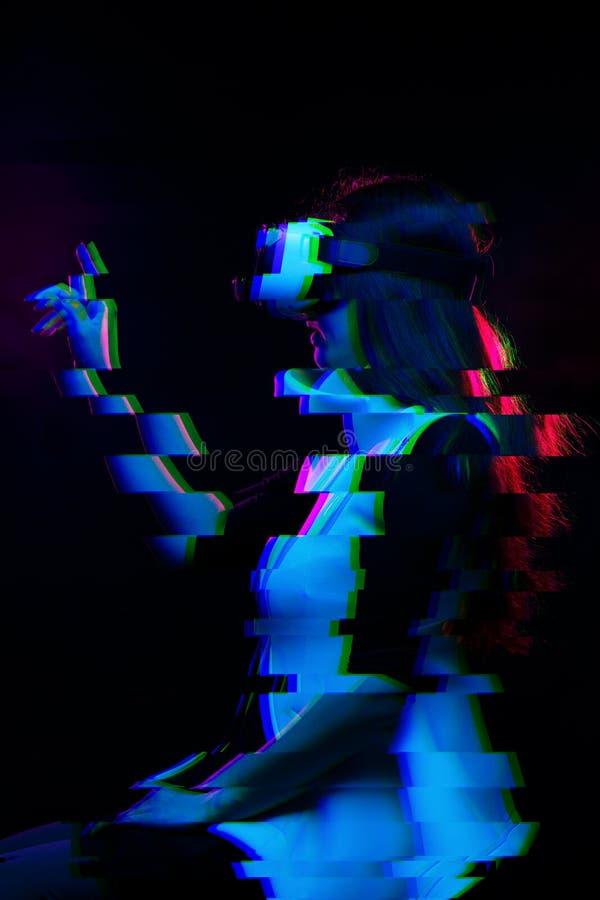 De vrouw gebruikt virtuele werkelijkheidshoofdtelefoon Beeld met glitch effect royalty-vrije stock afbeelding