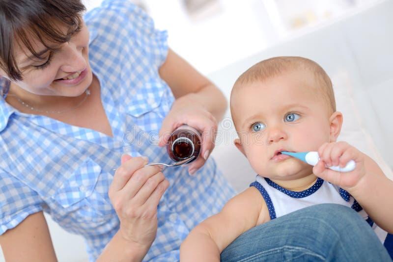 De vrouw geeft aan zieke babygeneeskunde stock afbeelding