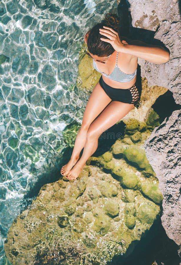 De vrouw gekleed in retro zwemt kostuumzon het buthing in de overzeese lagune stock foto's