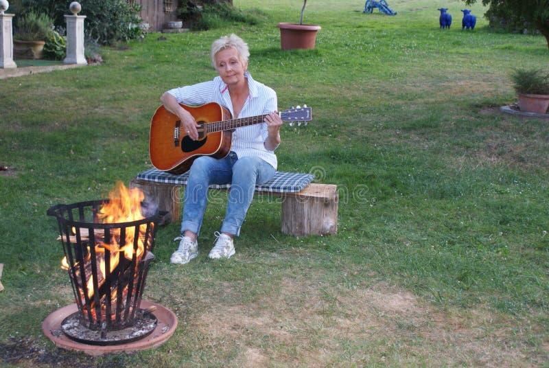 De vrouw is gelukkig over de aardige avond en speelt op de gitaar royalty-vrije stock foto's