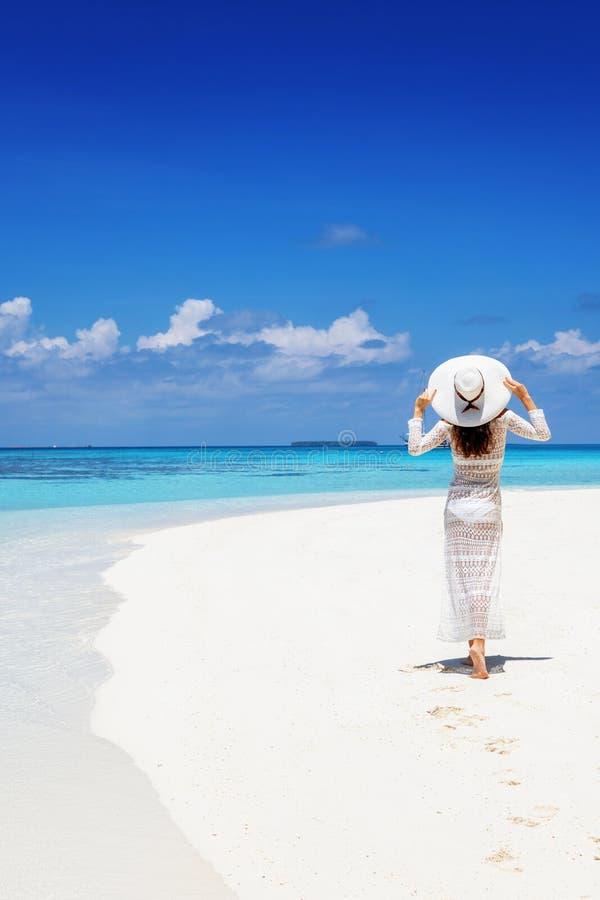 De vrouw geniet van het exotische landschap op een tropisch strand stock afbeelding