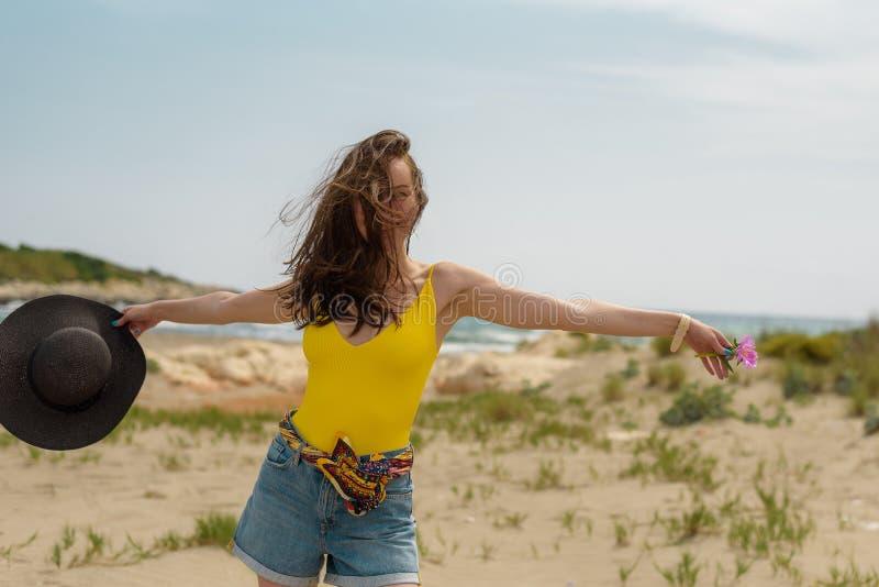 De vrouw geniet van lopend op het zand op de kust stock afbeelding
