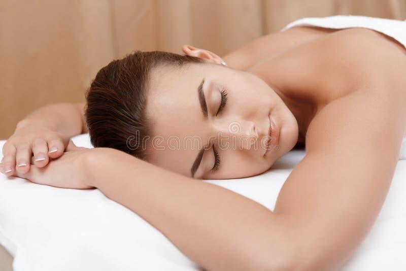De vrouw geniet van massage in kuuroordsalon stock foto