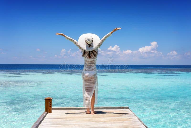 De vrouw geniet van de mening aan het tropische overzees die zich op een houten pijlerrand bevinden stock afbeelding
