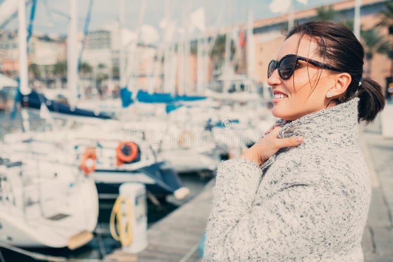 De vrouw geniet van met winderige zonnige de lentedag in de overzeese haven stock foto