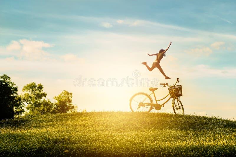 De vrouw geniet van vakantie in het park Zij sprong met geluk royalty-vrije stock afbeeldingen