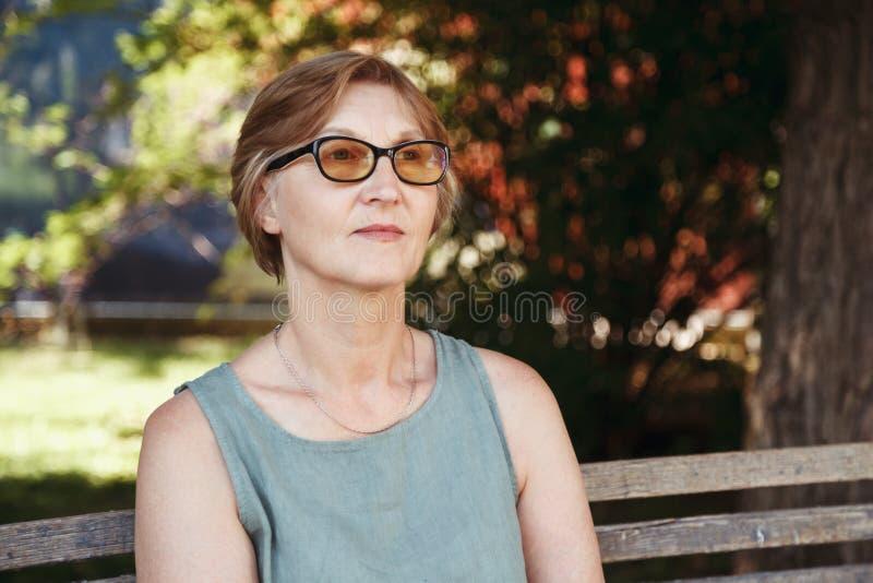 De vrouw de gepensioneerde die bril dragen heeft een rust in het pari royalty-vrije stock fotografie