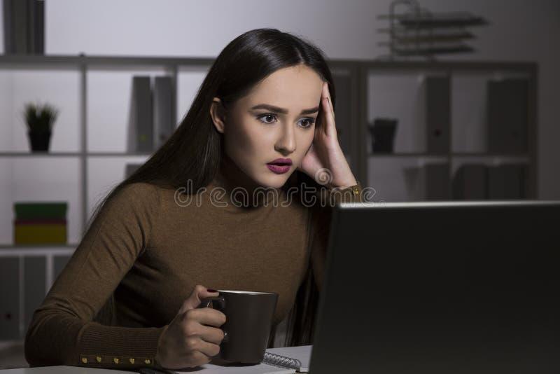 De vrouw is geschokt in een bureau bij nacht stock fotografie