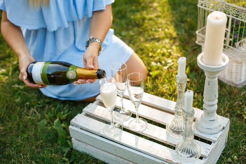 De vrouw giet champagne van fles aan glas op zonnig groen park stock foto's