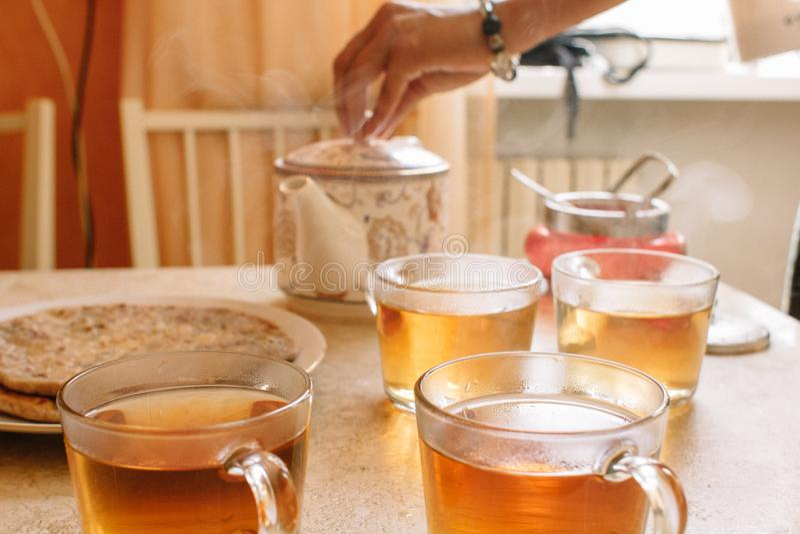 De vrouw giet hete thee van ceramische theepot in transparante glaskoppen stock afbeeldingen