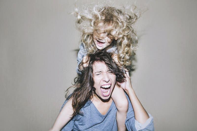 De vrouw gilt en debatteert met een kind op zijn schouders cli royalty-vrije stock afbeeldingen