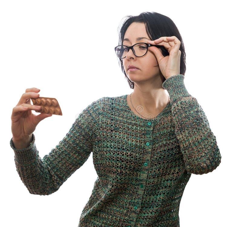 De vrouw in glazen bekijkt geneesmiddel royalty-vrije stock fotografie