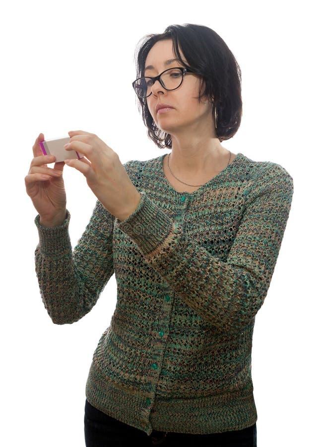 De vrouw in glazen bekijkt geneesmiddel royalty-vrije stock afbeelding