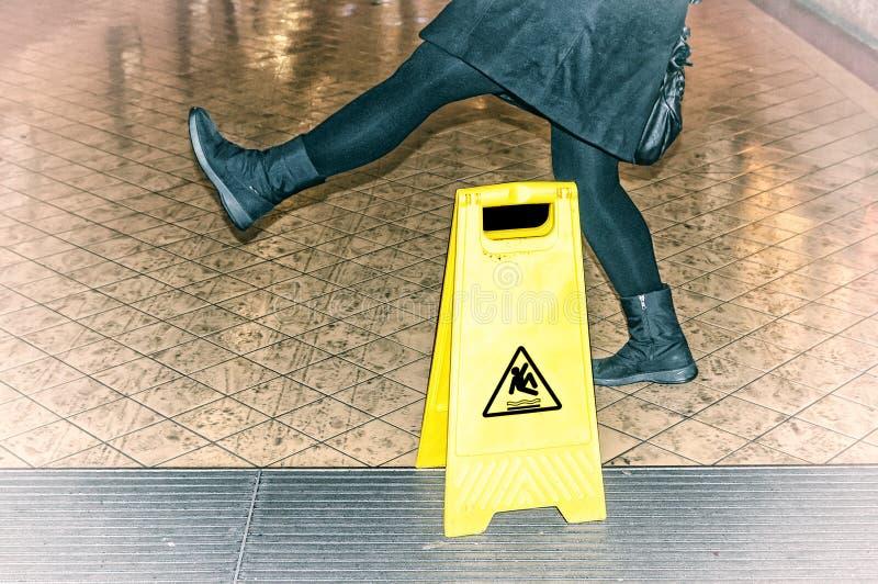 De vrouw glijdt bijna op een natte vloer uit stock fotografie