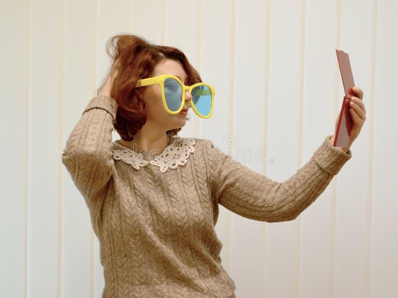 De vrouw in grote zonnebril doet omhoog haar, bekijkend zich in een spiegel stock afbeeldingen