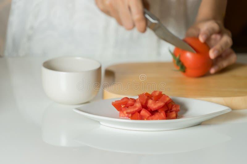 De vrouw is handen snijdend tomaat op houten raad stock afbeelding