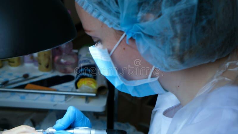 De vrouw in handschoenen doet pedicure en behandelt teennagelsopperhuid stock foto's
