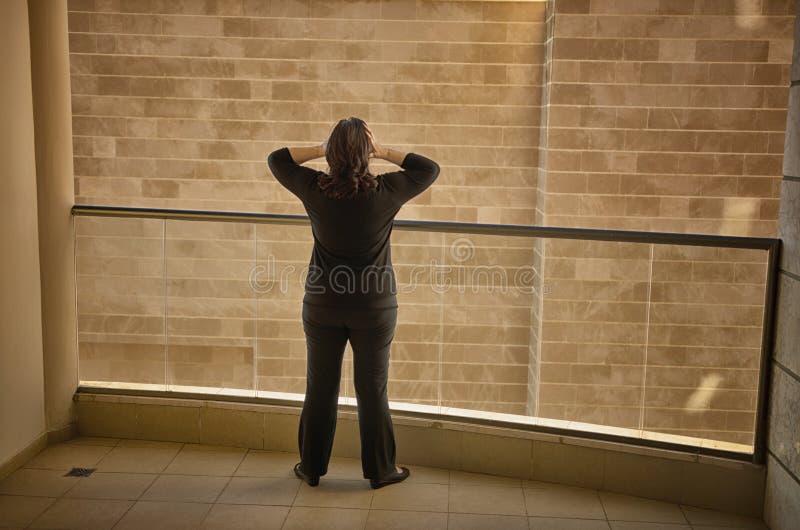 De vrouw heeft een claustrofobe aanval in haar vreselijk balkon stock afbeelding