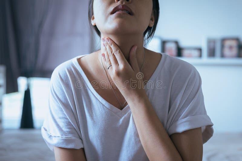 De vrouw heeft een keelpijn, Wijfje wat betreft hals met hand, Gezondheidszorgconcepten royalty-vrije stock foto's
