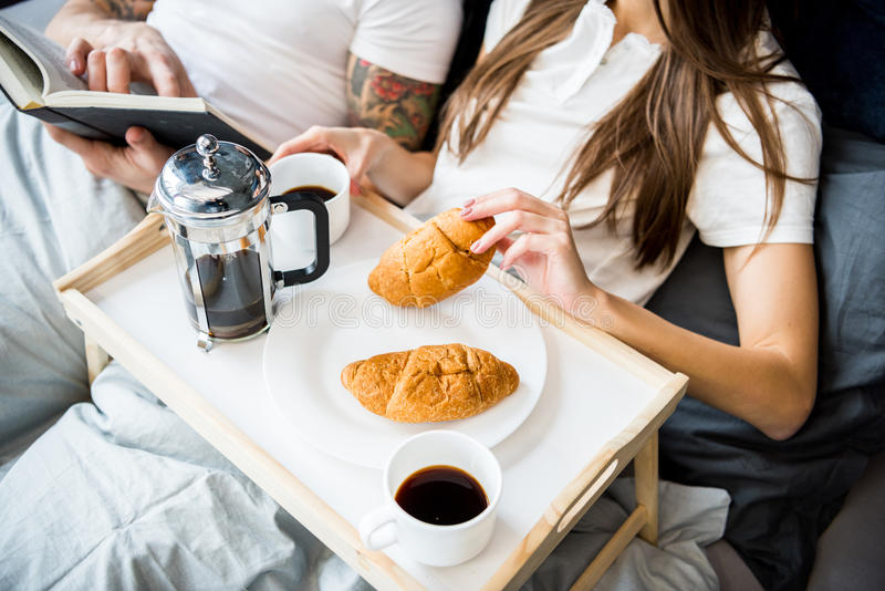 De vrouw heeft ontbijt in bed stock afbeeldingen