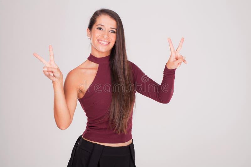 De vrouw heft haar vingers op en glimlacht stock fotografie
