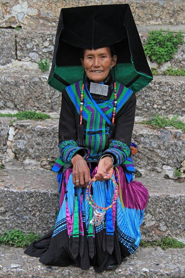 De vrouw in helder kleurrijk kostuum zit op stock afbeeldingen