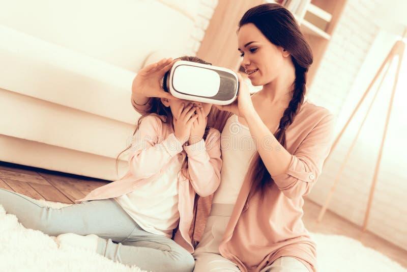 De vrouw helpt Meisje Virtuele Werkelijkheidsglazen houden royalty-vrije stock afbeelding