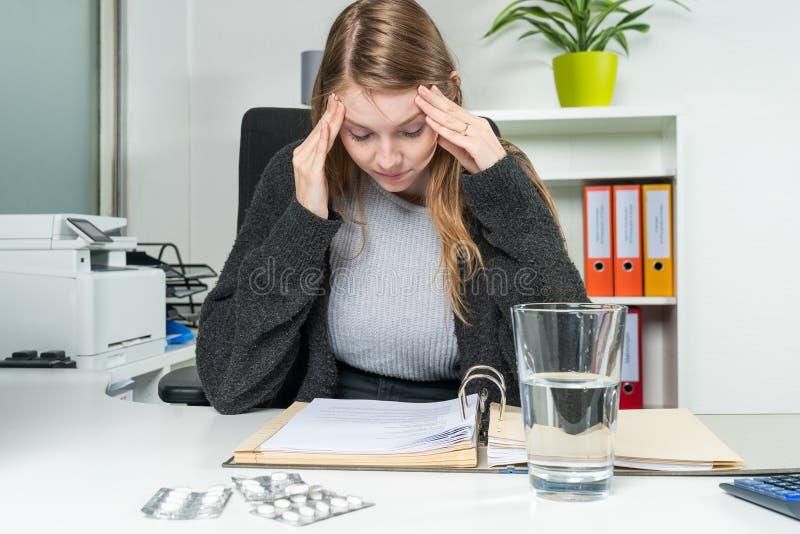 De vrouw in het bureau met hoofdpijnen leunt op de lijst stock foto's
