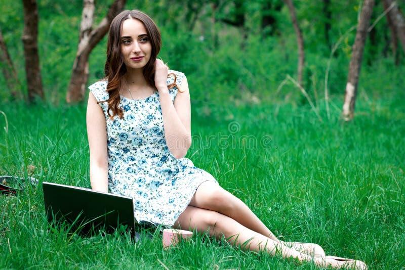 De vrouw of het meisje in een kleding, met laptop en hoofdtelefoons, zitten  royalty-vrije stock afbeelding