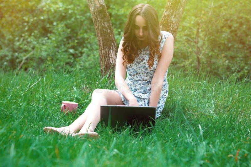 De vrouw of het meisje in een kleding, met laptop en hoofdtelefoons, zitten  royalty-vrije stock afbeeldingen