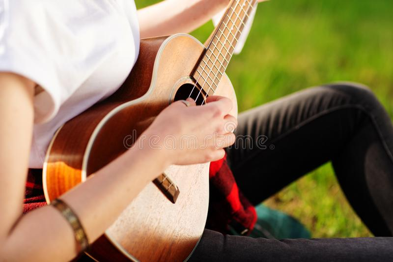 De vrouw het spelen gitaar, armband op het wapen Sluit omhoog foto stock afbeeldingen