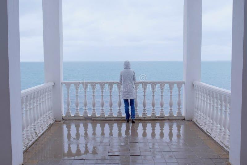De vrouw in het witte jasje bewondert op zee op mooi terras met overzeese mening Achter mening stock foto