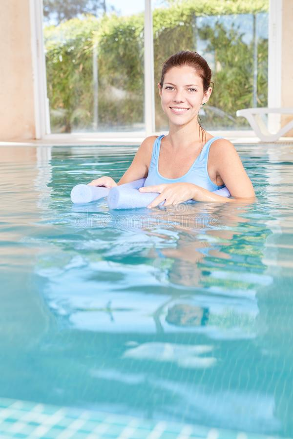 De vrouw in het zwembad doet watergeneeskunde stock foto