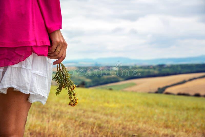 De vrouw houdt een bloem in haar hand stock afbeeldingen