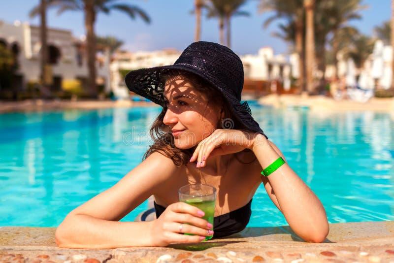 De vrouw houdt een cocktail in hotel zwembad De vakantie van de zomer Inclusief allen royalty-vrije stock foto's