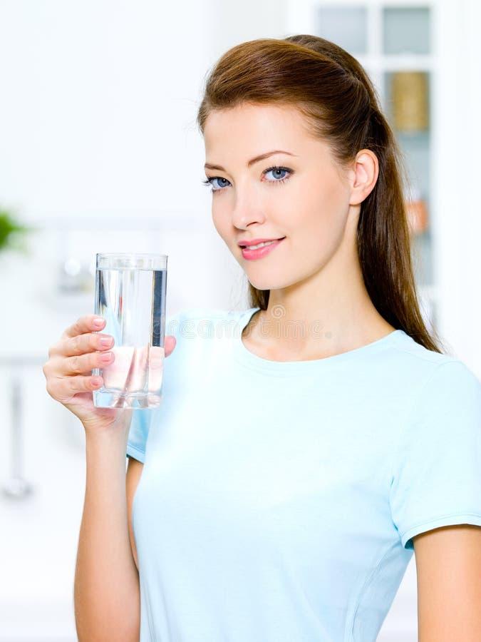 De vrouw houdt een glas met water