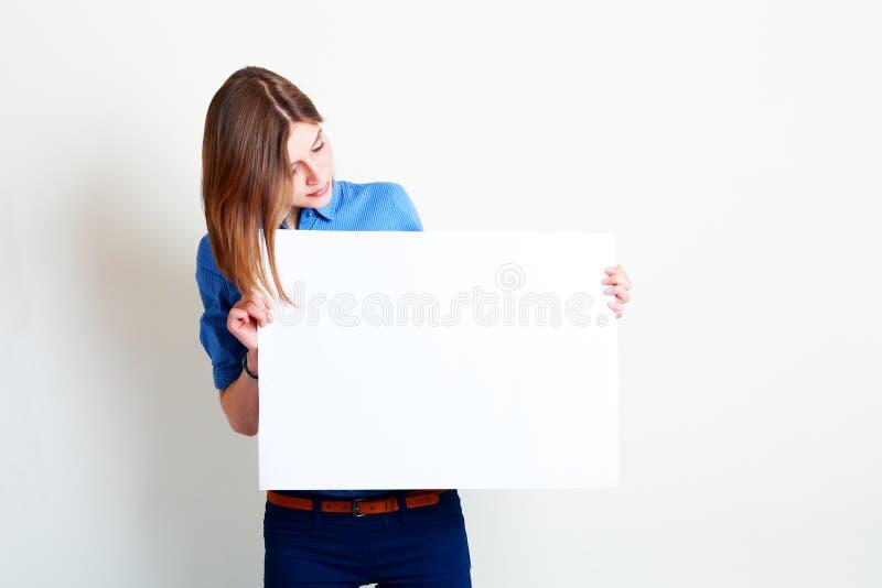 De vrouw houdt een grote lege kaart stand stock foto's