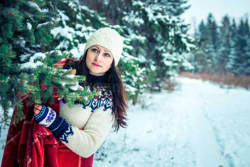 De vrouw houdt een kop van koffie in de winterbos stock foto