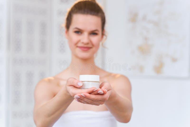 De vrouw houdt een organische natuurlijke room in haar hand om haar huid en rimpel van onzuiverheden te bevochtigen Schoonheid, l stock fotografie
