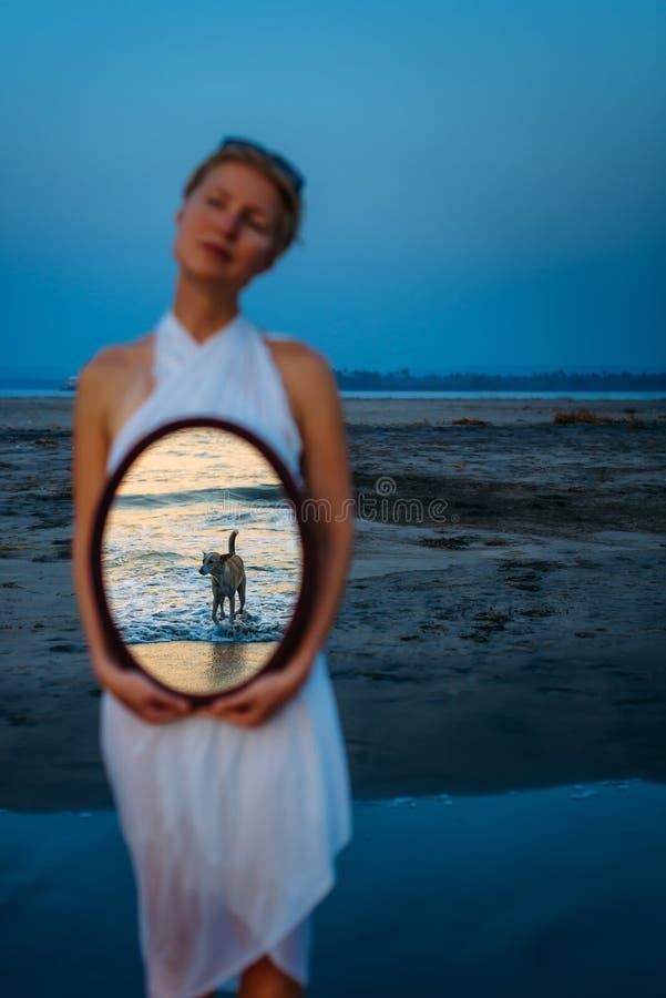 De vrouw houdt een spiegel waarin weerspiegelde overzees en hond in water, selectieve nadruk is Abstracte fotografie, concept de  royalty-vrije stock fotografie