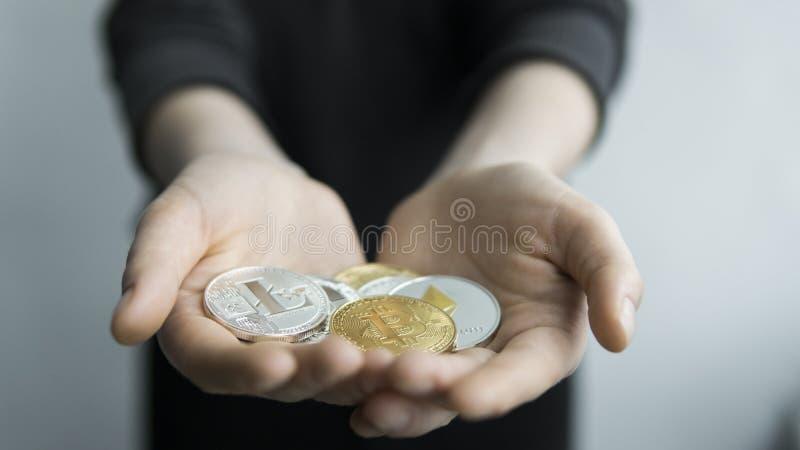 De vrouw houdt in handen fysieke cryptocurrencymuntstukken - gouden en zilveren bitcoins, ethereum en zilveren litecoin winst stock fotografie