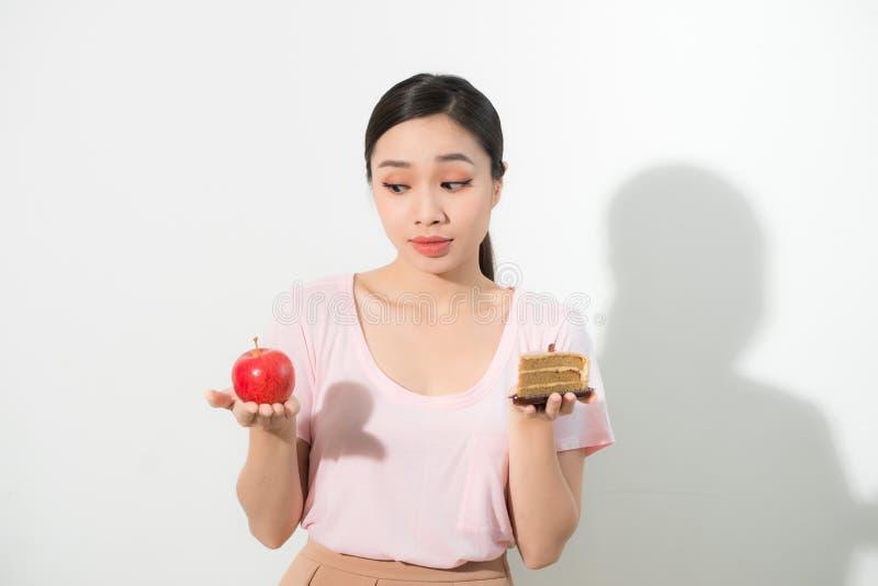 De vrouw houdt het in hand van de cakesnoepje en appel fruit kiezen, proberend om zich tegen verleiding te verzetten, om de juist stock foto's