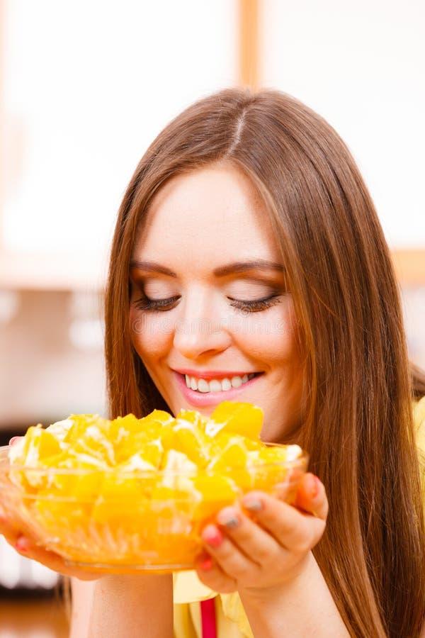 De vrouw houdt komhoogtepunt van gesneden oranje vruchten stock foto's