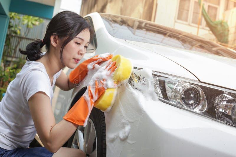 De vrouw houdt microfiber in hand en poetst de auto op stock fotografie