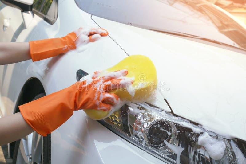 De vrouw houdt microfiber in hand en poetst de auto op royalty-vrije stock foto