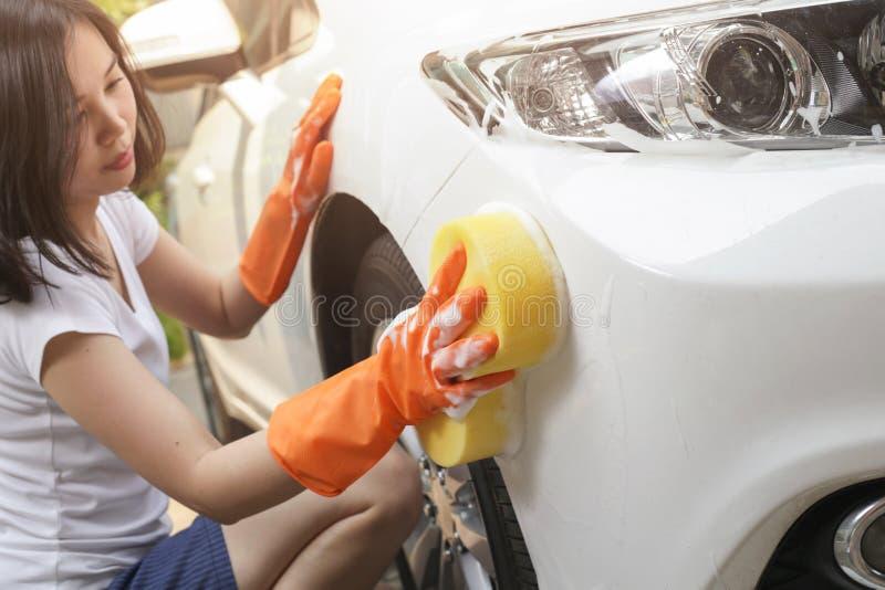 De vrouw houdt microfiber in hand en poetst de auto op stock foto's
