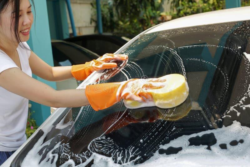 De vrouw houdt microfiber in hand en poetst de auto op stock afbeeldingen